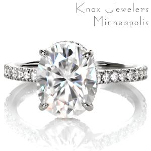 Design 3523 is a custom engagement ring of elevated elegance. A contemporary silhouette is finished with micro pavé diamonds placed into delicate u-cut settings. The dazzling oval moissanite center stone is cradled by a bejeweled four prong basket. This design is a streamline setting with extraordinary details.