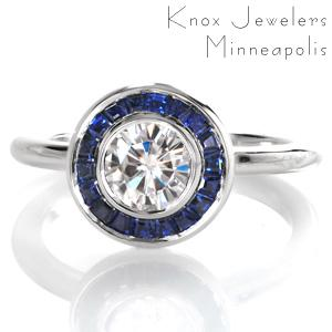 Design 3527 is a captivating custom engagement ring with clean lines and gemstone halo. A glittering 0.70 carat round diamond is held in a full bezel setting and surrounded by a custom halo comprised of perfectly placed tapered baguette blue sapphires. This impressive gemstone halo sits atop a classic rounded band.