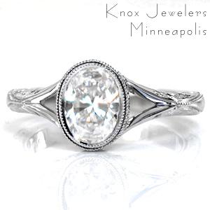 This artistic custom design features a bezel set oval center stone bordered with a double row of milgrain. The delicate split shank tapers into a hand engraved band. A decorative side halo frames the setting, with flush-set diamonds on the split of the shank as well. Hand wrought filigree curls complete this ring.