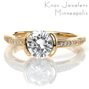 This elegant contemporary design features a half bezel center setting that reveals the full profile of the center stone from the side. The delicate band is set with small round brilliant diamonds, and features open pockets that could be filled with hand wrought filigree curls for an added vintage appeal.