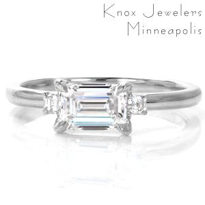 Elegant simplicity creates a gorgeous three stone design with an East-West set emerald cut center diamond and small, asscher cut side stones. The mesmerizing mirrored facets of these step-cut stones are complimented by the smooth, high polished luster of the metal.