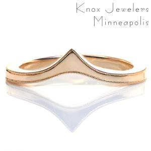 An elegant band, Design 3557 is uniquely shaped to be worn as a contoured wedding band against an engagement ring, alone, or as part of a stacking set. The band tapers as it reaches the top before flaring out again into a point. The top edges of the piece are delicately hand detailed with a beaded milgrain texture.