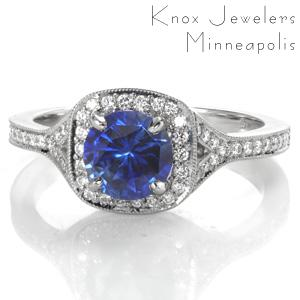 Lush colored sapphire adds a regal air to this modern halo engagement ring design. A narrow diamond band flares and separates near the top to seamlessly flow into the diamond halo. A beaded texture called milgrain has been hand applied to the edges for a sophisticated look.