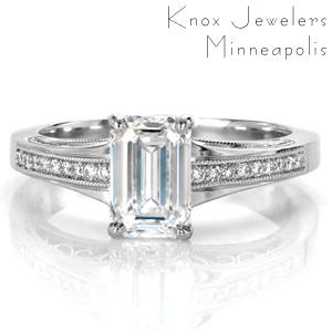 Design 3567 is an elegant antique inspired piece shown with an emerald cut center diamond. The flared band compliments the elongated shape of the step cut stone, while milgrain edged rows of round brilliant diamonds add sparkle to the top of the band. The sides are detailed with graceful, flowing hand wrought filigree.