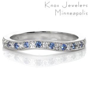 Pale, light blue sapphires add a delicate touch of color do this contoured wedding band design. A custom design, this band has been crafted with a squared Euro shank base. The gentle contour of the top is always custom drawn to fit the ring it will sit with. Beaded milgrain texture adds a vintage touch to the edges.