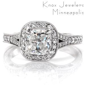 Classic antique details are brought to life in exquisite beauty with this split-shank halo engagement ring. The center is shown as a cushion cut diamond surrounded by a micro pavé double sided halo. The band is additionally adorned with delicate hand engraving, hand wrought filigree curls, and milgrain detail.