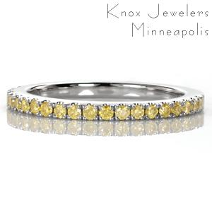 Yellow diamonds add a vibrant, colorful detail to this classic wedding or anniversary band. The U-cut micro pavé setting style keeps each gem held securely while allowing for the maximum amount of visibility and sparkle. The high polished metal of the band adds a beautiful shine to the already dazzling band.