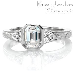 Design 3577 is a beautiful flared design featuring an emerald cut center diamond held in a half-bezel setting. The top of the antique inspired band is adorned with hand engraved scroll patterns and edged with a beaded milgrain texture. Clusters of round brilliant diamonds frame the center stone.