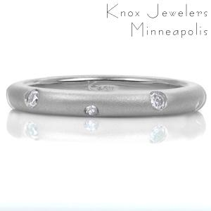 Sparkling like stars, small flush set diamonds alternate in size as they dance around this contemporary band. The contrast between the dazzling gems and the luster of the matte sandblasted finish highlights the complimentary pairing with a feeling of modern elegance.