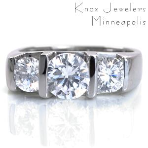 Bliss is a perfect representation of contemporary beauty. This modern engagement ring design is shown featuring a half-bezel set 1.00 carat round brilliant cut center stone framed with 0.50 carat side diamonds. The wide band is wide for an added sense of strength. The Euro-shank base mimics the top shape of the band.