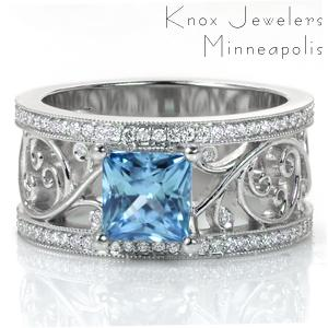 This breathtaking design features a large, open filigree pattern set with small diamonds in some of the curls.The micro pavé diamond rails are edged in milgrain for added vintage appeal. Shown here with a unique 1.70 carat princess cut sapphire, Design 3598 is a statement piece.