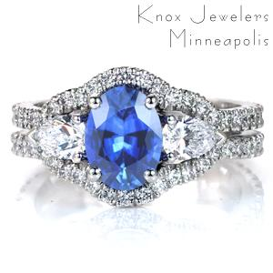 Featuring a luscious oval sapphire center stone, Design 3600 is a unique take on a triple halo design. The micro pavé diamond band flows up and flares out to contour around the trio of center stones. A pair of pear cut diamonds flank the sapphire center stone with dazzling beauty.