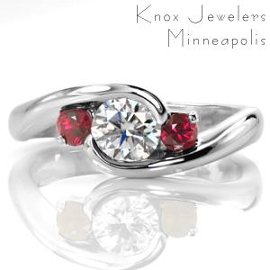 Lush red rubies flank a round brilliant center diamond in this contemporary design. The center stone is wrapped in a half-bezel setting with a tapering band. The smooth, high polished metal of the band adds a shiny luster to the design to compliment the sparkle from the gem stones.