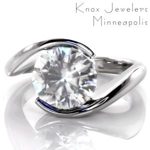 Our Ripple design is shown here with a 2.50 carat round cut center stone. This modern design features a delicate, high polished band that wraps around the solitaire gem to form the center setting. The luster of the metal band for this half bezel design adds a beautiful compliment to the sparkle of the center stone.