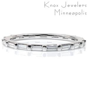 Chic, delicate diamond bands are perfect for stacking! This eternity span band features long, narrow, baguette cut diamonds. Each stone is set in a shared half-bezel setting style. This design combines modern minimalism with Art Deco elegance for a gorgeous band whether worn alone or with another piece.