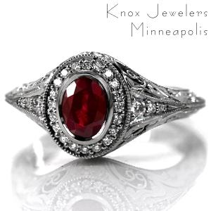 Design 3623 is shown featuring a bezel set 1.20 carat oval cut ruby center stone. A micro pavé halo frames the gem and blends seamlessly into the flared knife edge band. The sides of the band are elegantly detailed with relief style hand engraving, and pockets of hand wrought filigree curls.