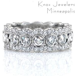 Design 3629 is a lavish eternity span diamond band. The mixed setting styles and varied stone sizes create a  pattern of overlapping halos around larger bezel set interior gems. The scalloped diamond rails that form the partial halos are held in U-cut style prong settings.