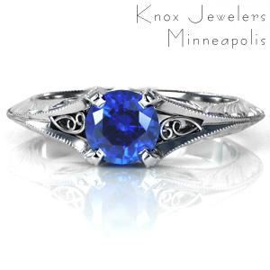 Elegant antique inspired details come together to create a stunning solitaire engagement ring featuring a lush blue sapphire. The flared knife edge band is ornately detailed with hand engraved patterns and hand wrought filigree curls. The band flows up to form the center prongs with milgrain textured edges.
