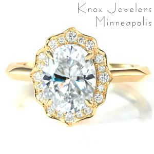 Shown with a 2.00 carat oval cut diamond, this majestic engagement ring features a scalloped halo set with mixed sizes of round brilliant cut diamonds. The knife edge band blends with the subtle points of the halo and adds to the vintage appeal of the design.