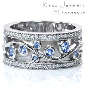 This stunning wide band design features an elegant filigree design perfect for showing off lushly colored gem stones. The pale blue sapphires shown are set in wrapping-bezels as the filigree flows between two micro pavé diamond rails. Beaded milgrain texture frames the diamonds and adds to the vintage appeal.