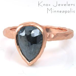 This solitaire design is shown with a pear shaped, rose cut, salt and pepper diamond. The band is hand hammered and carved to create a faceted texture that compliments the top-facets of the stone. The dark gray-black of the center stone looks stunning with any of the precious metal colors.