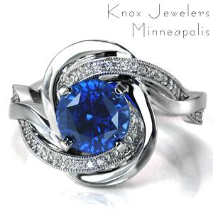 Evoking thoughts of the rippling ocean waves, Design 3651 features intertwining bands that flow around the blue sapphire center stone to form a unique halo. The contrast between the diamond set band and the high polished band adds to the motion of the piece.