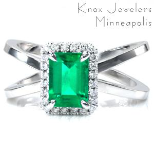 Design 3658 is shown with an emerald cut emerald gemstone center surrounded by a halo of round brilliant cut diamonds. The wide split shank design of the band is high polished to add contrast to the sparkle of the diamonds in the halo.
