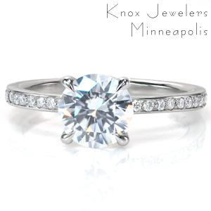 Divine is a timeless diamond engagement ring style. This elegant band features narrow, high polished rails to either side of the side diamonds. The crown flows out of the band to form a secure claw prong setting around the center stone, while sitting up high enough to easily fit with a wedding band.