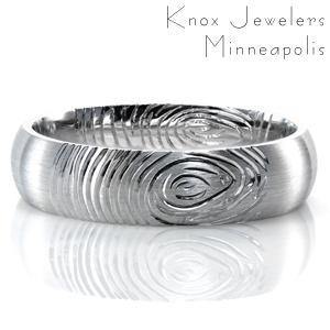 Adding the fingerprint of your future spouse to the design of your wedding band is a beautiful way to keep a piece of them with you wherever you go. This custom domed band is shown with a comfort fit interior. The brushed finish on the outside of the band offers contrast to the lines of the print.