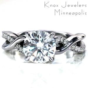Design 3673 is a uniquely twisting split shank design featuring one band set with diamonds and one band high polished. Around the sides of the center setting small diamonds have been set for added sparkle! This design is shown here with a 1.50 carat round brilliant cut center stone.