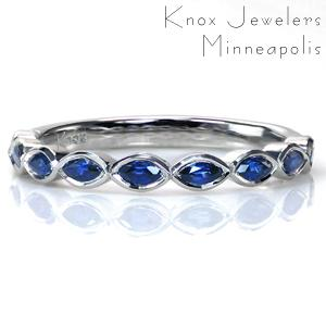 For a stunning take on a gemstone band, consider using uniquely shaped stones to create a geometric pattern. These marquise cut blue sapphires add a beautifully rich details in the form of the color and the scalloped shape created by setting them East-West.