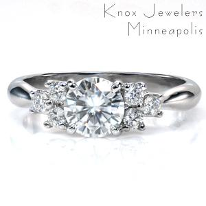 A 0.80 round brilliant center stone is accented by two clusters of three diamonds on each side. The unique lattice setting cradles the stones and blends seamlessly into the high polish reverse taper band. The beautiful curves of the band and the setting add a feminine touch to a classic design.