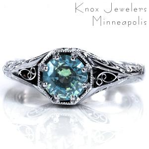 A 1.0 carat green sapphire is the centerpiece of Design 3700. Milgrain detailing is applied around the stone as well as along the band. Pockets of hand wrought filigree curls are visible from both top and side views, and the band also features intricate hand engraving. Surprise diamonds complete this custom ring.