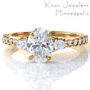 A 1.0 carat oval diamond is flanked by two pear shaped diamonds in Design 3707. The unique band features bezel set round diamonds and a high polish finish. A glamorous five petal diamond detail adds extra sparkle and flair under the custom center setting.