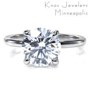 A dazzling 2.50 carat center stone is simply showcased in an elegant four prong setting. A decorative basket adds a bit of extra sparkle and flair and gives the profile view added interest. Set in gleaming platinum, this classic solitaire is a timeless statement of elegance and grace.