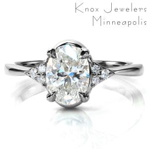 A stunning oval diamond is elegantly set in a reverse taper band. A cluster of three diamonds accent the 1.20 carat center stone, adding just a touch of sparkle to this antique inspired design. The highly polished band with its clean lines draws the eye into the center of this beautiful ring.