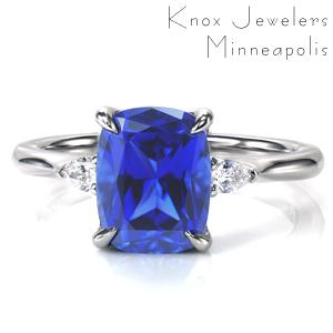 A brilliant blue 2.70 carat cushion cut sapphire is the star of this stunning design. The center stone is set in a classic four prong setting accented by sparkling, pear cut diamonds on each side. A simple, high polish band tapers slightly into the center, drawing the eye to the dazzling center.