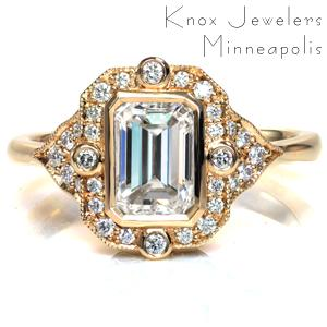 Etta features a 1 carat emerald cut diamond in a vintage inspired design. Beadset and bezel set diamonds accent the bezel set center stone, and milgrain detailing is applied by hand around the unique halo. Platinum filigree curls are formed by hand and placed into pockets under the setting, creating a two tone effect.