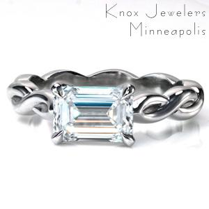 Design 3740 features a stunning east-west set 1.0 carat emerald cut diamond in a simple, 4 claw prong setting. The unique, high polished band twists in a repeating infinity sign pattern that spans the entire ring. A modern take on the solitaire, this ring is a new classic!