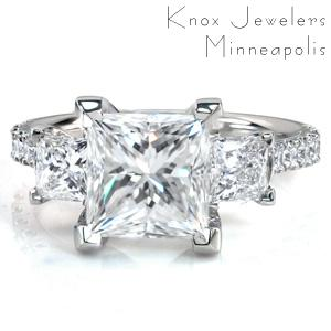 Not your average three stone ring, Design 3753 is sure to catch your eye! It features a staggering 2.70 carat Princess cut center stone, with over a full carat in side stones. The center stone is flanked with two more Princess cut diamonds, and round brilliant stones adorn the cathedral band.