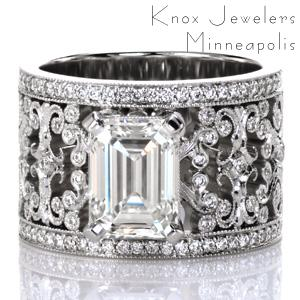 Design 3755 is a stunning example of sophisticated artistry. A 2 carat emerald cut diamond is set atop the intricately detailed wide band. Broad filigree flourishes curl and hold bezel set round diamonds. Each turn of metal has hand applied milgrain detail for a vintage look. Rows of bead set diamonds frame the band.