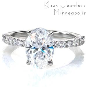 A 2 carat oval is set simply atop a charming shared prong band with round brilliant diamonds spanning half way around the ring. This classic style delivers lots of sparkle, and it is designed so that any wedding band design will sit flush against it.