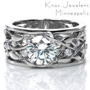 A dazzling 1.20 carat diamond is nestled in unique, petal shaped prongs. The intertwining leaf and vine design of the band is accented with round brilliant diamonds, sparkling between the vines. This wide band is finished with thin rails on each side of the ring and a high polish shine.