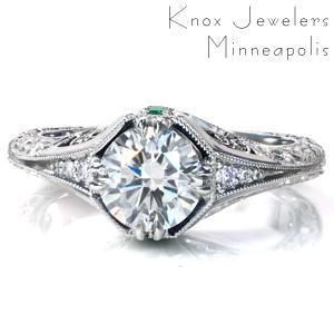 A 1.20 carat diamond is framed by 4 sets of double prongs and a unique under halo in Design 3765. The flared band features graduated diamonds leading to a knife edge, intricate relief style engraving, and hand applied milgrain detail. This vintage inspired beauty is finished with filigree curls and a surprise emerald.
