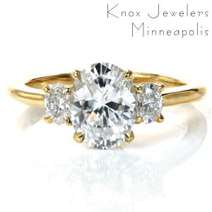 Our Charlotte design is a classic three stone engagement ring with a modern update. A 1.5 carat oval diamond is flanked by oval diamonds on each side creating a perfectly symmetric look. The simple basket setting provides a clean look, and the high polish of the band complements the brilliant diamonds beautifully.