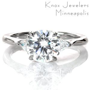A modern take on the classic three stone engagement ring, Ava frames a 1.2 carat center diamond with two trillion shaped side stones. The elegant curves of the basket setting flow perfectly into the high polished tapered band, drawing your eyes toward the stunning diamonds.