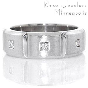 Crafted in 14k white gold, the Manhattan band has a total of 0.24 carats of flush set princess cut diamonds. The diamonds are set into the center of three stations which are separated by high polished grooves. The band has rounded edges for a tailored fit.