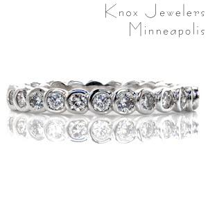 This full bezel diamond eternity band has a modern look and clean lines. With over 0.83 carats of round brilliant diamonds, the design forms a seamless row of sparkle. The band is crafted in 14k white gold with the smooth curves of the bezels and a high polish finish for added comfort and shine.