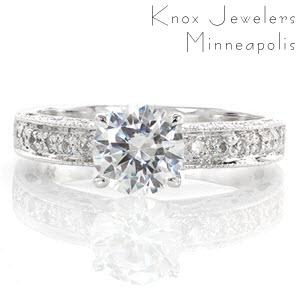 The Adorable design is simply charming! A .80 carat round center diamond is accented by bead-set side stones on the top of the band. The sides feature bezel set diamonds and cut outs, including a heart shape on the side of the center stone. All the edges are detailed in milgrain to add texture.
