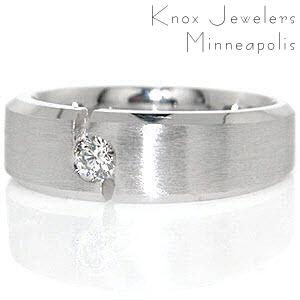 Dallas is a modern wedding band created in 14k white gold. The design features a 0.19 carat round brilliant diamond flush set between a unique notched channel. A matte finish center is contrasted by high polish beveled edges that give this contemporary band a distinguished look.